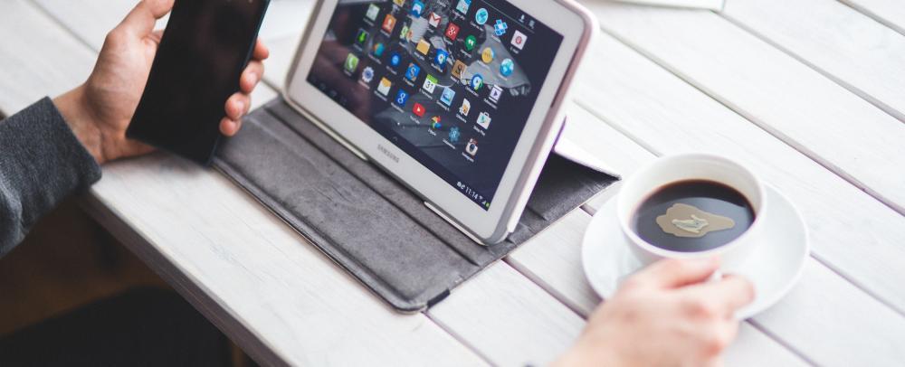 Persona al computer con una tazza di caffè